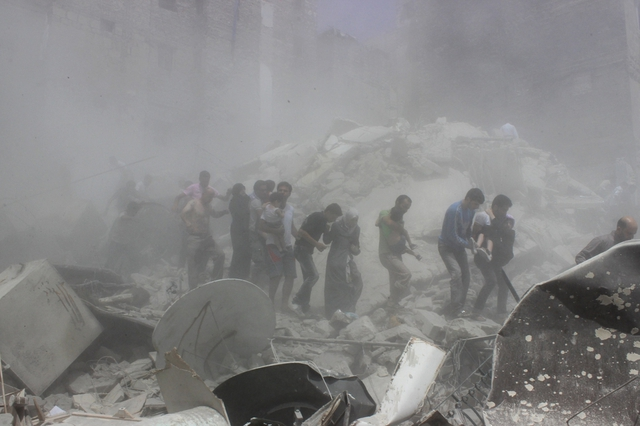 Những người đàn ông giúp đỡ sơ tán dân thường khỏi khu vực bị trúng đạn pháo của quân đội chính phủ ở thành phố Aleppo, Syria.