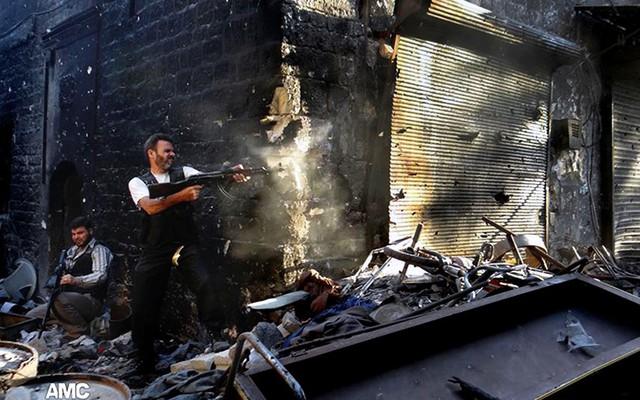 Một chiến binh của quân đội Syria tự do xả súng về phía quân đội chính phủ trong cuộc giao tranh ở thành phố Aleppo, Syria.
