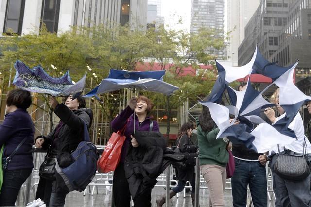 Mọi người xếp hàng dưới mưa bão để chờ mua iPad Air bên ngoài cửa hàng Apple ở New York, Mỹ.