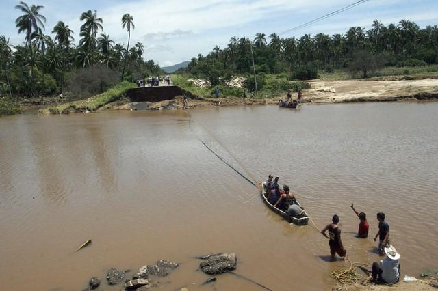 Mọi người qua sông bằng thuyền dây kéo gần một cây cầu bị phá hủy do mưa lũ ở Coyuca de Benitez, Mexico.