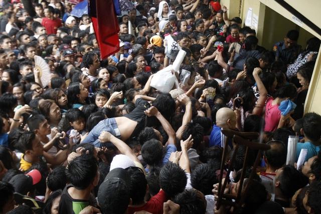 Một phụ nữ bị ngất được đám đông nhấc lên cao để đưa ra ngoài trước văn phòng Ủy ban bầu cử ở Manila, Philippines.