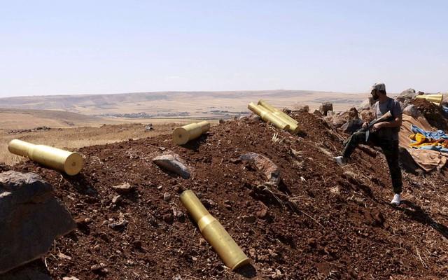 Một binh sĩ trung thành với chính phủ của Tổng thống Bashar al-Assad đứng cạnh vỏ đạn pháo cạnh ngôi làng Tal El-Tineh ở Aleppo, Syria.