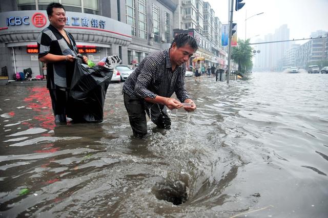 Hai người đàn ông dọn rác mắc tại một hố ga thoát nước trên đường phố ngập lụt do mưa lớn sau siêu bão Utor ở Dương Giang, Trung Quốc.