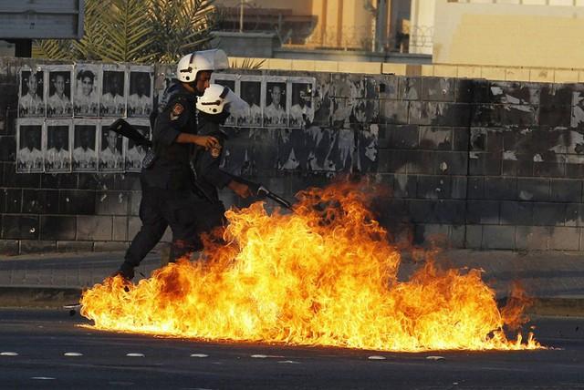 Cảnh sát chống bạo động đi qua một đám cháy do bom xăng ném bởi người biểu tình chống chính phủ ở Manama, Bahrain.