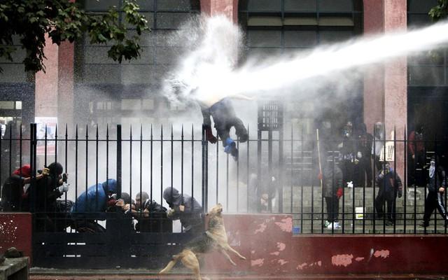 Một sinh viên bị cảnh sát phun vòi rồng khi đang trèo qua hàng rào sát trong cuộc biểu tình đòi cải cách hệ thống giáo dục công ở Santiago, Chile.