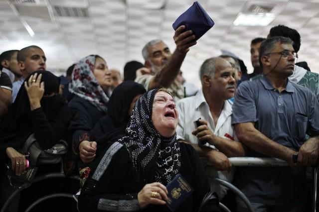 Một phụ nữ khóc khi đứng chờ tại cửa khẩu Rafah với hy vọng có thể từ Dải Gaza sang Ai Cập.