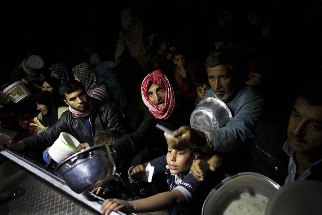 Những người dân xếp hàng chờ nhân thực phẩm miễn phía trong một trại tị nạn gần Azaz, Syria, ngày 23/10/2012.
