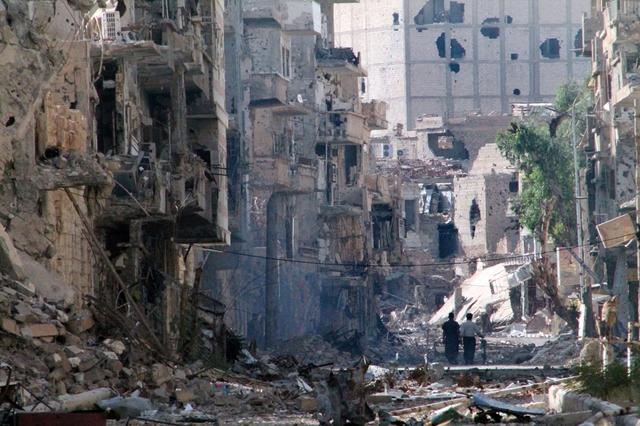 Những người đàn ông đi dọc đường phố với những ngôi nhà bị phá hủy bởi bom đạn ở Deir Ezzor, Syria.