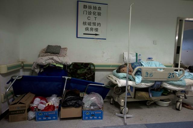 Bệnh nhân phải nằm trên giường ngoài hành lang tại một bệnh viện quá tải ở Bắc Kinh, Trung Quốc.