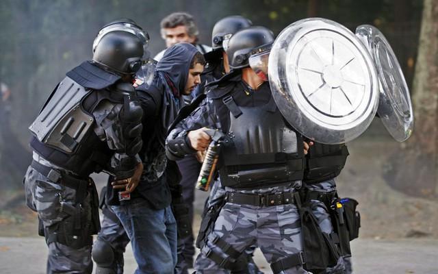 Cảnh sát bắt giữ một người biểu tình bên ngoài sân vận động Maracana ở Rio de Janeiro, Brazil. Những người biểu tình phản đối chính phủ chi quá nhiều tiền vào việc xây dựng sân vận động cho World Cup sẽ diễn ra tại nước này vào năm tới.
