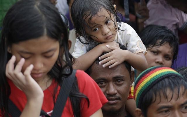 Bé gái dường như kiệt sức vì đói trong khi cùng bố chờ nhận hàng viện trợ.
