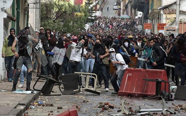 Đám đông người biểu tình đụng độ với cảnh sát chống bạo động trên đường phố ở Bogota, Colombia. Người biểu tình yêu cầu chính phủ giảm giá xăng dầu và tăng trợ cấp.