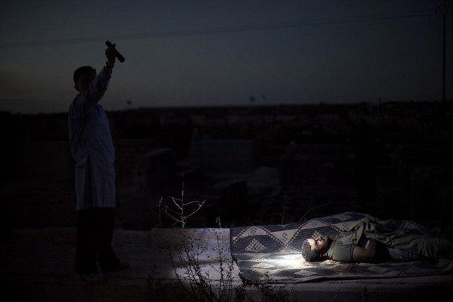 Một người đàn ông soi đèn pin vào một chiến binh phiến quân thiệt mạng do bị trúng đạn pháo của quân chính phủ ở Aleppo, Syria, ngày 13/10/2012.