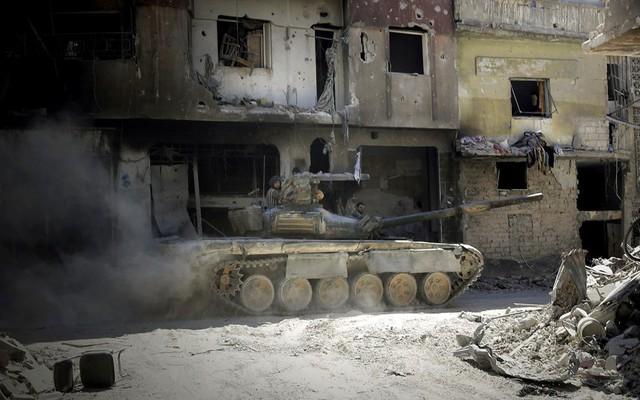 Các binh sĩ của quân đội chính phủ tuần tra trên xe tăng tại khu vực al-Khalidiyah ở thành phố Homs, Syria.