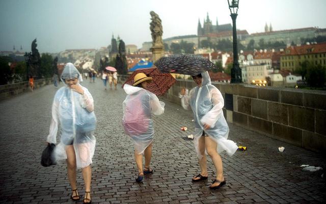 Khách du lịch đối phó với mưa và gió mạnh trên cầu Charles ở Prague, CH Czech.