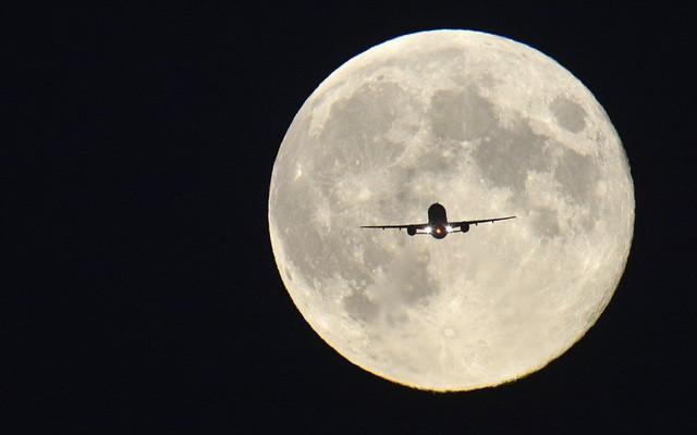 Một chiếc máy bay chở khách in bóng giữa Trăng Rằm, trong khi chuẩn bị hạ cánh xuống sân bay Heathrow ở London, Anh.