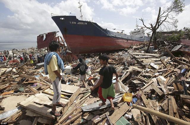 Trẻ em tìm kiếm những đồ con dùng được trên những ngôi nhà đổ nát ven biển.