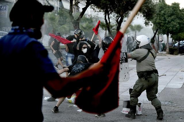 Cảnh sát chống bạo động đụng độ với những người biểu tình trên đường phố ở ngoại ô thủ đô Athens, Hi Lạp.