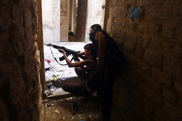 Một chiến binh của lực lượng phiến quân dạy con trai sử dụng súng tại thành phố Aleppo, Syria.