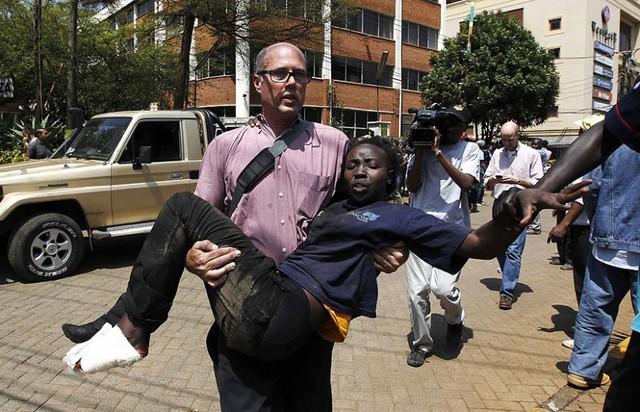 Một nhà báo phương Tây giúp đỡ nạn nhân bị thương.