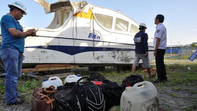 Đồ đạc, tư trang cá nhân của 30 người đi trên canô H29-BP được đưa ra khỏi cabin vào chiều 4-8 - Ảnh: Đông Hà