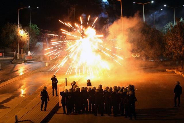 Cảnh sát chống bạo động đứng trước pháo sáng được ném bởi những người biểu tình ở Ankara, Thổ Nhĩ Kỳ.