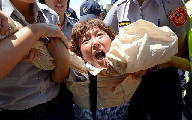 Cảnh sát bắt giữ một phụ nữ tham gia biểu tình phản đối hiệp định thương mại giữa Đài Loan và Trung Quốc bên ngoài tòa nhà quốc hội ở thủ đô Đài Bắc.