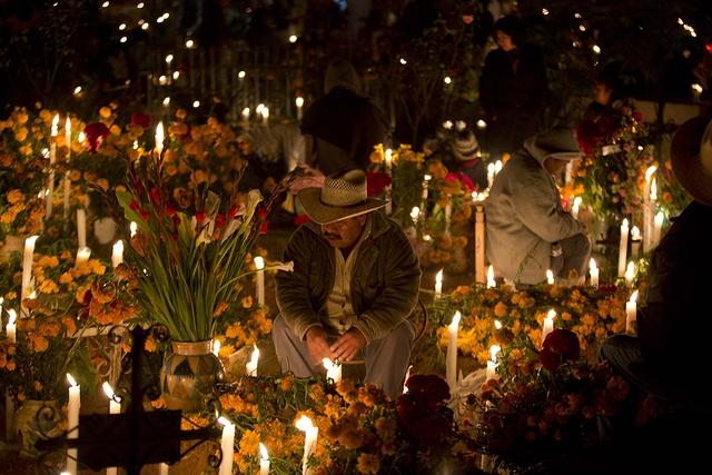 Một người đàn ông ngồi cầu nguyện bên mộ người thân trong ngày Day of the Dead ở Atzompa, Mexico.
