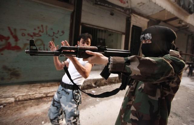 Một nữ chiến binh được lực lượng phiến quân Syria hướng dẫn sử dụng súng tại thành phố Aleppo.