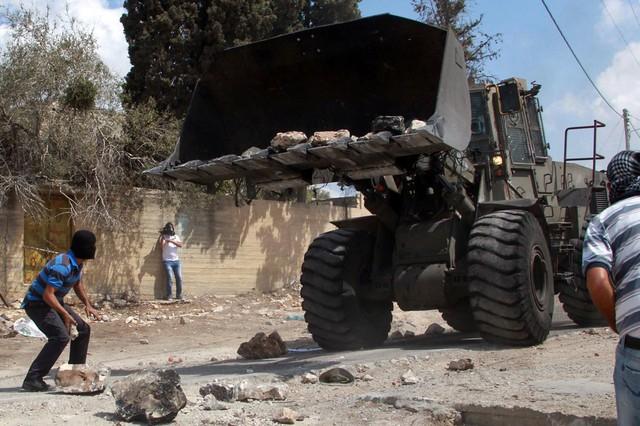 Một người Palestin bịt mặt chuẩn bị ném đá vào xe ủi đất của quân đội Israel trong cuộc biểu tình chống xây dựng các khu định cư của người Do Thái tại thành phố Nablus, Bờ Tây.