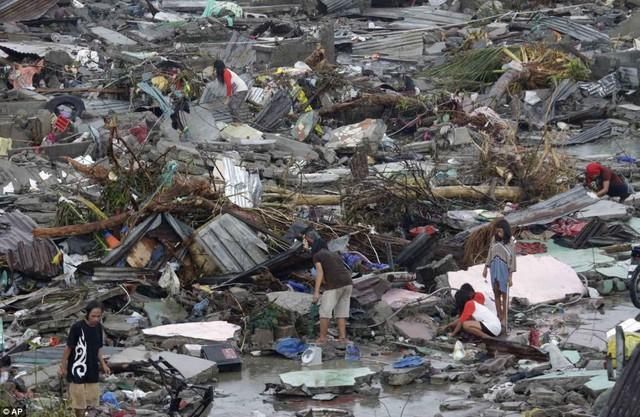 Trẻ em cùng người lớn tìm kiếm thức ăn trong đống đổ nát.