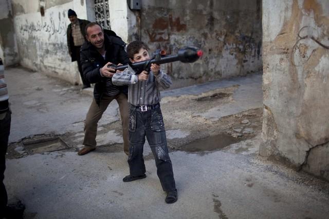 Một người đàn ông dạy cậu bé Bilal, 11 tuổi, cách sử dụng rocket đồ chơi tại Idlib, Syria, ngày 4/3/2012.
