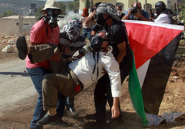 Một người đàn ông Palestin được đưa đi sau khi bị thương trong cuộc đụng độ với lực lượng quân đội Israel ở Bờ Tây.