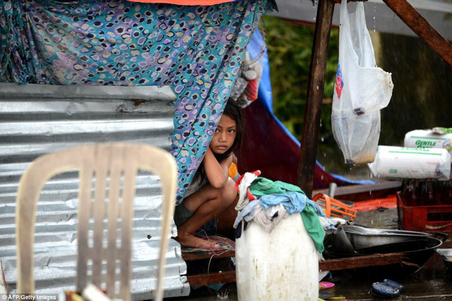 Bé gái co ro ngồi trong lều tạm nhìn ra ngoài trời mưa ở thành phố Tacloban.