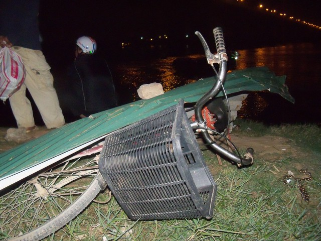 Chiếc xe đạp của người thợ tìm thi thể nạn nhân được đè tấm tôn lên