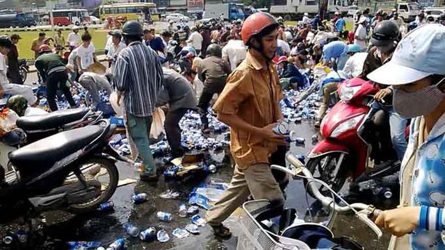 Hàng trăm người xông vào cướp bia tại khu vực vòng xoay Tam Hiệp, TP Biên Hòa, Đồng Nai trong sự bất lực của tài xế. (Ảnh: Tuổi trẻ)