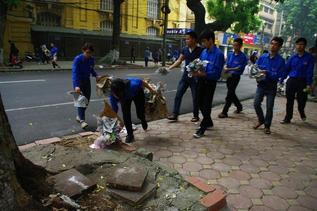 Thanh niên tình nguyện dọn dẹp rác trên con phố gần nhà tang lễ.