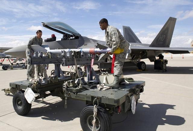 Hai lính Mỹ đang chuẩn bị lắp quả đạn tên lửa không đối không tầm ngắn dẫn đường hồng ngoại AIM-9 lên chiếc F-22. Ngoài 2 khoang dưới bụng máy bay, F-22 còn thiết kế với 2 khoang nhỏ ở gốc cánh. Hai khoang nhỏ này dùng để lắp 2 đạn tên lửa AIM-9.