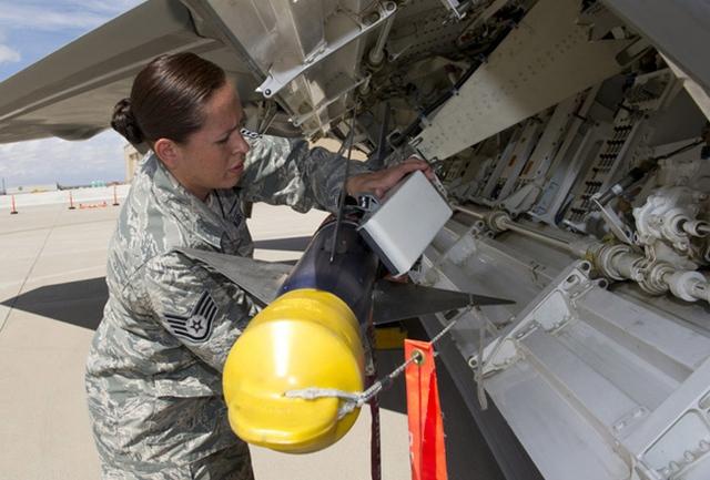 Nữ kỹ thuật viên lắp quả đạn tên lửa AIM-9 lên khoang nhỏ F-22.