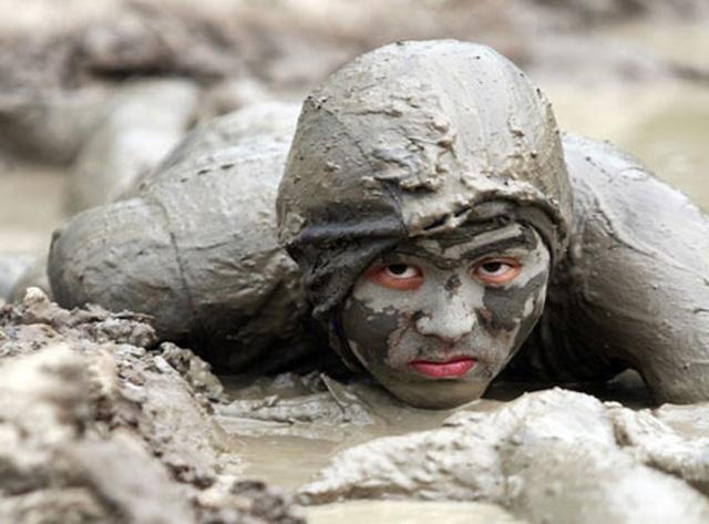 Một người lính đặc công được ngụy trang bằng bùn đất đang lặng lẽ áp sát mục tiêu.