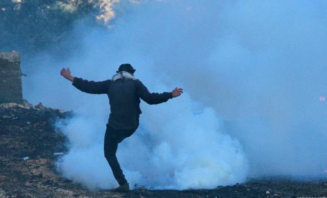 Một người Palestine đá lựu đạn hơi cay trở lại các binh sĩ Israel trong cuộc biểu tình phản đối khu định cư mở rộng của người Do Thái ở Nablus, Bờ Tây.