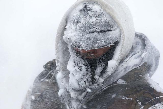 Một công nhân bị bao phủ bởi băng và tuyết khi dọn tuyết trên hè phố ở Detroit, Mỹ.