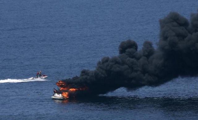 Nhân viên cứu hộ quan sát tàu bốc cháy gần bãi biển Barra da Tijuca ở Rio de Janeiro, Brazil.