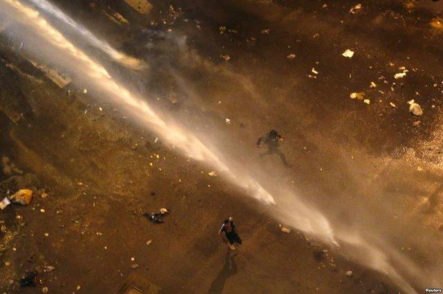 Người biểu tình chống chính phủ bỏ chảy để tránh vòi rồng phun nước của cảnh sát trên quảng trường Altamira ở Caracas, Venezuela.