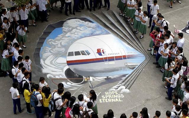 Học sinh đứng xung quang bức tranh 3D của chiếc máy bay MH370 bị mất tích được vẽ trên sân của một trường học ở thành phố Makati, Philippines.