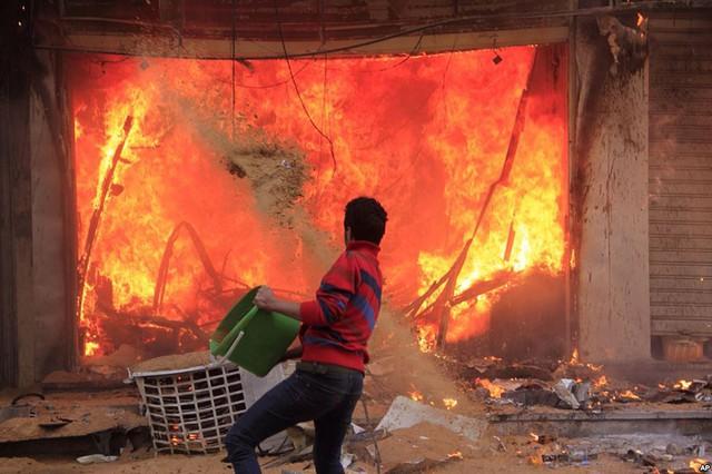 Một người dân cố gắng dập tắt đám cháy gây ra bởi những người ủng hộ  Tổ chức Anh em Hồi giáo tại thành phố Giza, Ai Cập.