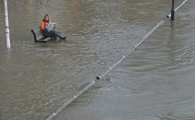 Một phụ nữ ngồi trên ghế bên bờ sông Thames ngập lụt ở Staines, Anh.
