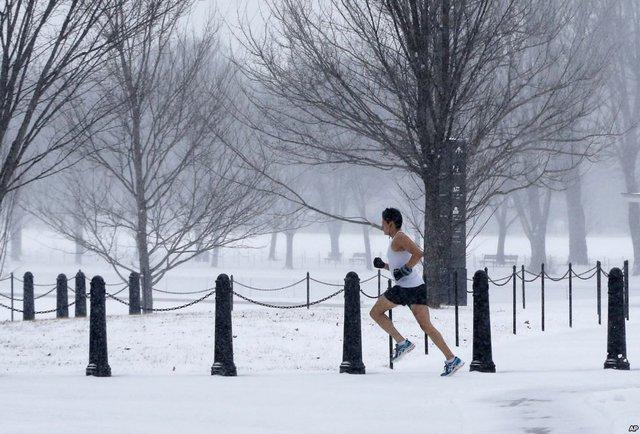 Một người đàn ông chạy thể dục dưới mưa tuyết trong công viên ở Washington, Mỹ.