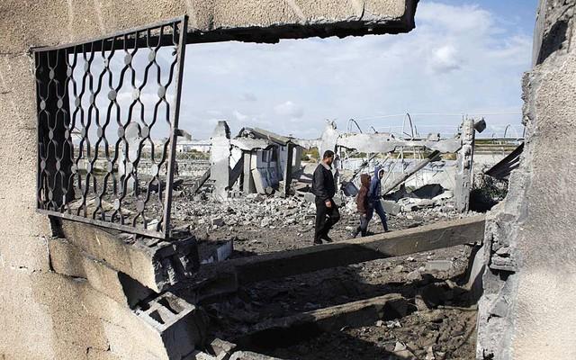 Những người dân Palestine kiểm tra hiện trường vụ không kích của Israel ở Rafah, miền nam Gaza.