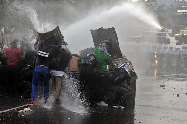 Người biểu tình che chắn khỏi vòi rồng của cảnh sát trên đường phố ở Caracas, Venezuela.
